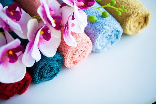 Toallas y orquídea coloreadas en la tabla blanca en cuarto de baño.