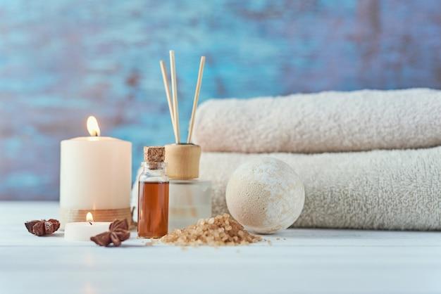Toallas, velas y aceite de masaje en mesa blanca