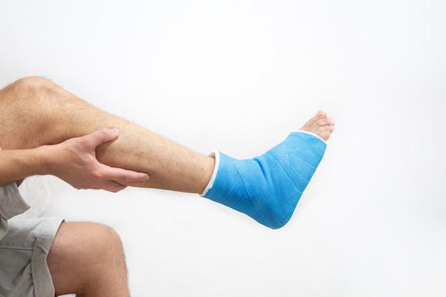 Tobillo entablillado azul. yeso de pierna vendada en paciente masculino sobre fondo blanco aislado. concepto de lesiones deportivas.