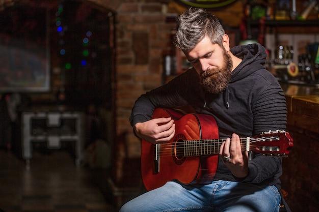 Toca el guitarrista barbudo. tocar la guitarra. hombre de barba hipster sentado en un pub. música en vivo. guitarras y cuerdas. hombre barbudo tocando la guitarra, sosteniendo una guitarra acústica en sus manos. concepto de música.