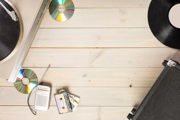 Tocadiscos tocadiscos de vinilo; disco compacto; cinta de cassette y radio en mesa de madera.