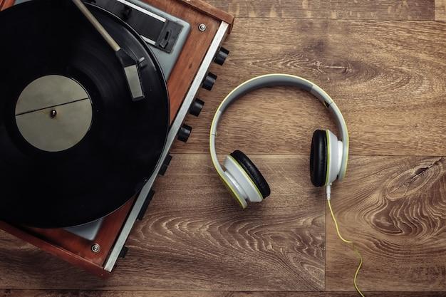 Tocadiscos de vinilo retro con auriculares estéreo en un piso de madera