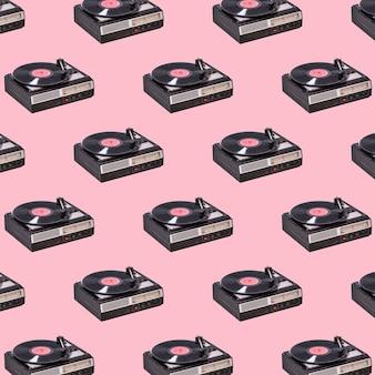 Tocadiscos de vinilo vintage y discos de vinilo sobre fondo rosa. tecnología de sonido retro.