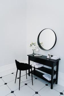 Tocador en el baño con espejo y toalla.
