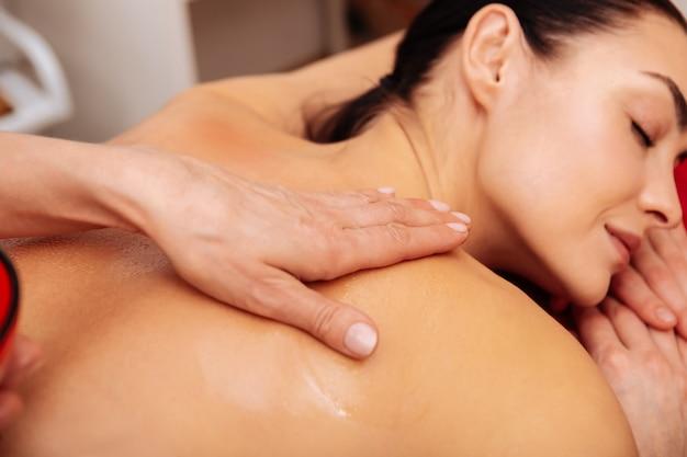 Tocando al cliente de nuevo. mujer tranquila y relajada recibiendo masajes en la espalda con aceite perfumado durante un procedimiento suave