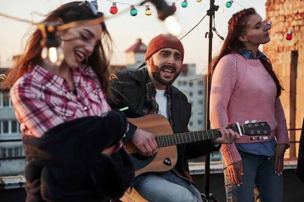 Tocando el alma. tres amigos disfrutan cantando canciones de guitarra acústica en la azotea