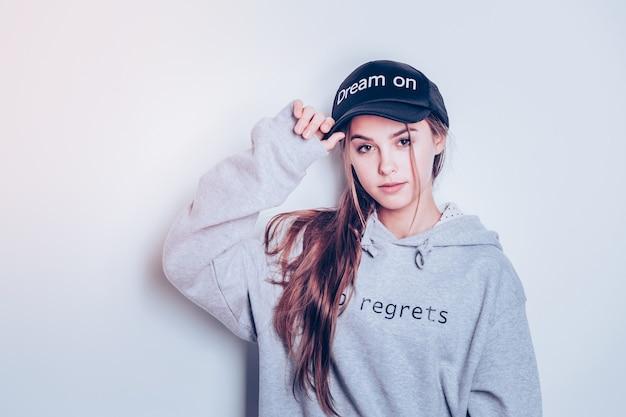 Tocando gorra negra. encantadora dama adolescente posando en piezas de moda con palabras impresas en ellas