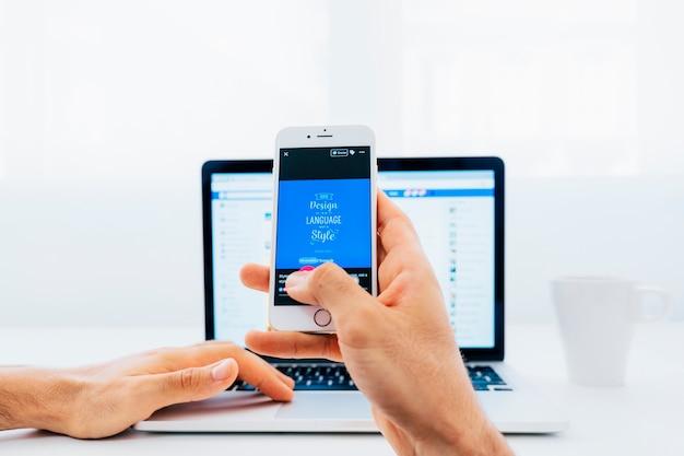 Tocando la pantalla del móvil con el portátil de fondo