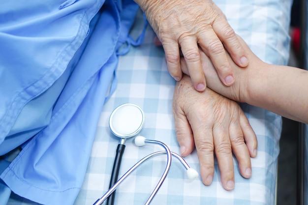 Tocar la mano asiática anciana o anciana paciente con amor, cuidado, ánimo y empaque