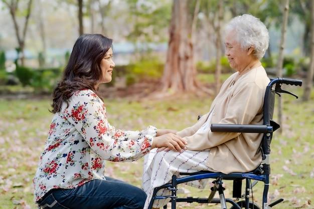 Tocar las manos paciente mujer asiática senior con amor.