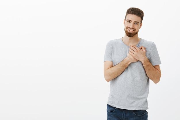 Tocaste mi corazón. retrato de guapo moreno caucásico masculino elegante y carismático con barba sosteniendo los brazos en el pecho agradecido y agradecido sonriendo ampliamente con amor sincero y admiración