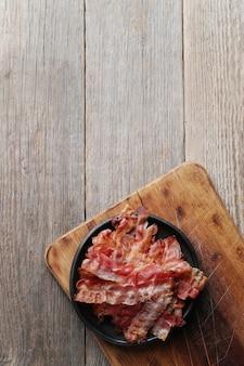 Tocino frito en placa negra y tabla de cortar de madera