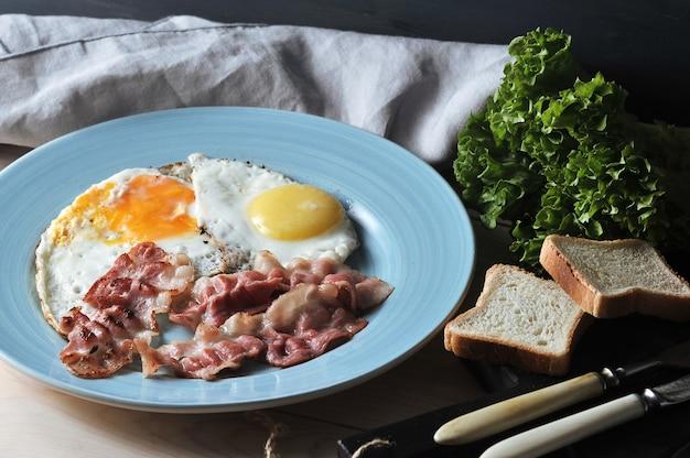 Tocino y huevos en un plato azul, tostadas