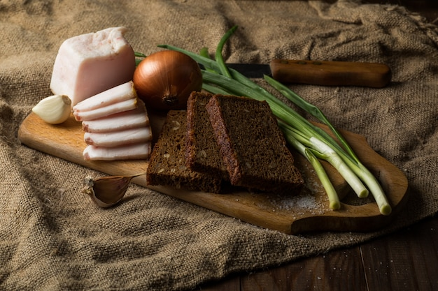 Tocino, pan de centeno sobre tabla de madera.