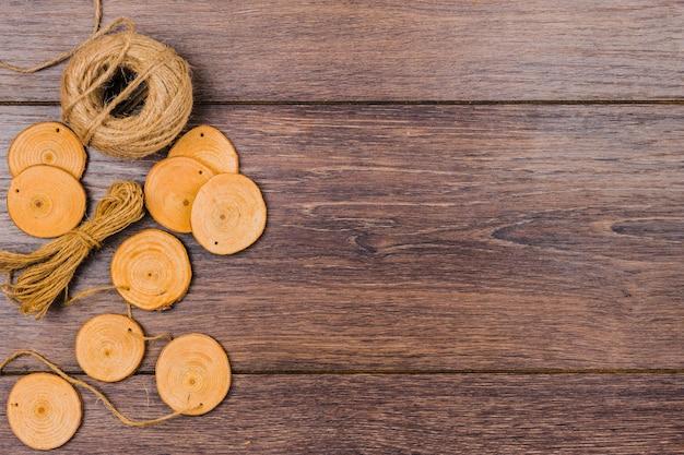 Tocón de árbol circular y carrete de yute sobre fondo de madera