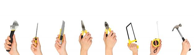 Toda la herramienta mano que sostiene aislado en la pared blanca