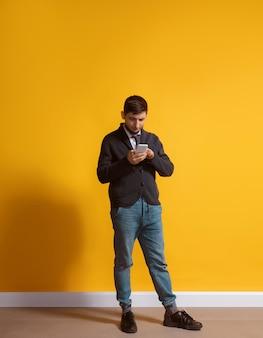 Toda la vida en gadget. hombre caucásico joven con smartphone, sirviendo, charlando, apostando. retrato de cuerpo entero aislado en la pared amarilla. concepto de tecnologías modernas, millennials, redes sociales.