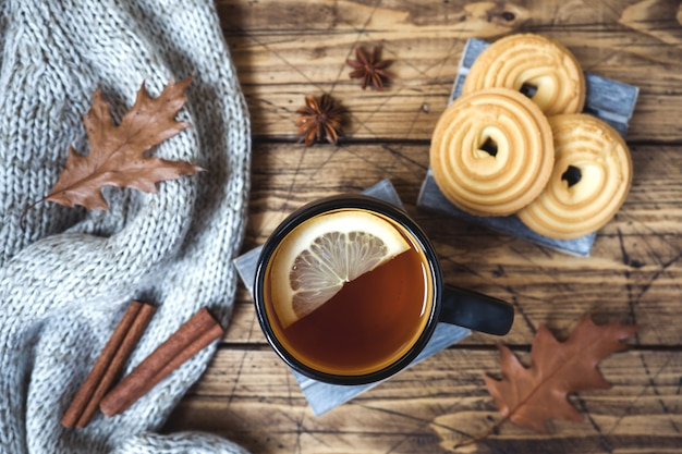 Todavía del otoño vida con la taza de té, de galletas, de suéter y de hojas en superficie de madera.