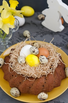 Todavía de pascua vida, torta de pascua con los huevos teñidos en una jerarquía, narcisos en una taza en un fondo concreto