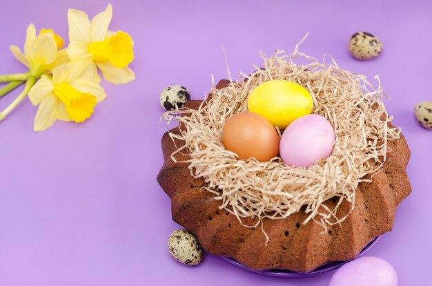 Todavía de pascua vida, torta de pascua, pollo y huevos de codornices, en un fondo violeta.