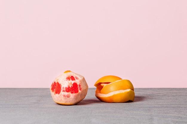 Todavía la vida de un pomelo pelado con su cáscara al lado sobre un mantel gris y un fondo de color rosa