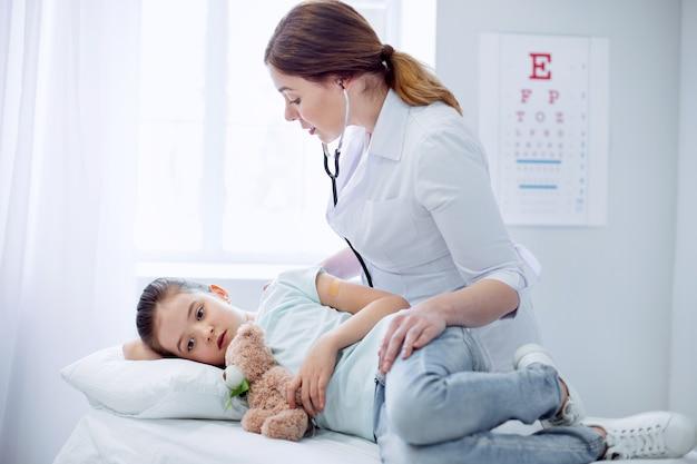 Todo está bien. preocupado médico femenino hábil inclinado sobre la niña que miente y toca el oso de peluche