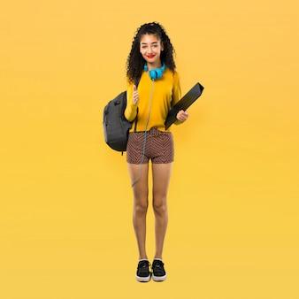 Todo el cuerpo de la chica adolescente estudiante con el pelo rizado, agitando las manos para cerrar un buen trato