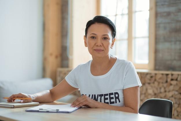 Todo hecho. voluntaria hermosa ambiciosa sentada a la mesa mientras escribe un documento y mira a la cámara