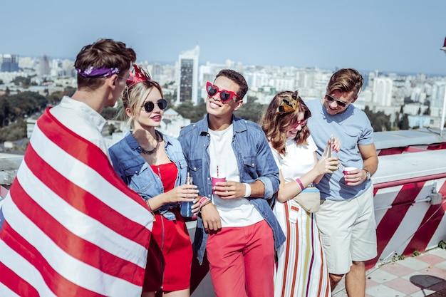 En todos los oídos. jóvenes alegres que pasan el fin de semana con placer mientras disfrutan de una fiesta en la azotea