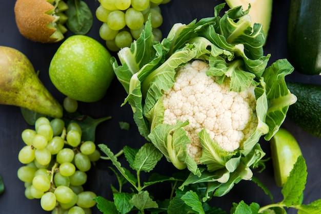 Todos los vegetales verdes y frutas sobre fondo oscuro