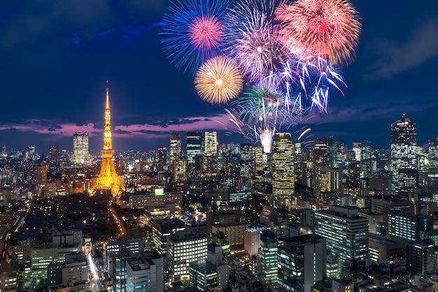 Tokio por la noche, año nuevo de los fuegos artificiales que celebra sobre el paisaje urbano de tokio por la noche en japón