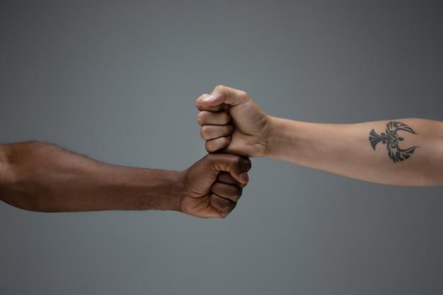 Tolerancia racial. respeta la unidad social. manos africanas y caucásicas gesticulando aislado en gris