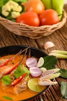 Tom yum kung thai sopa picante de camarones con hierba de limón, limón, galanga y chile en mesa de madera, comida de tailandia