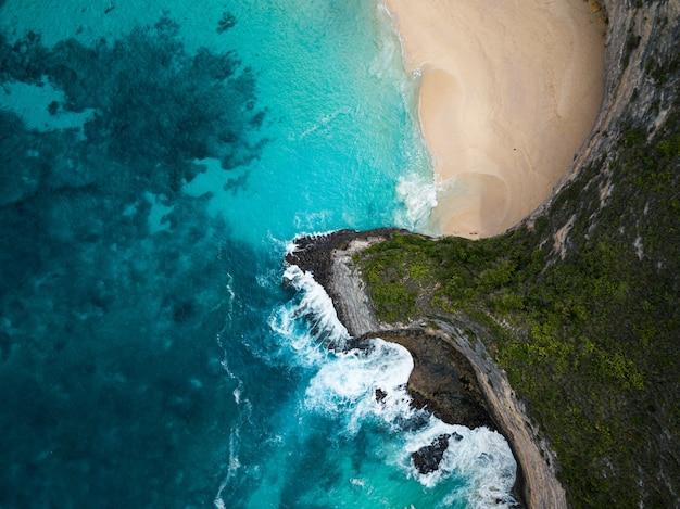Toma aérea de los acantilados cubiertos de vegetación rodeados por el mar, perfecto para fondos
