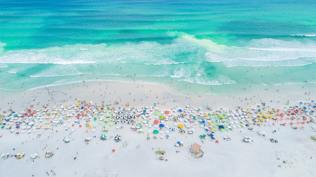 Toma aérea bloqueada de olas rompiendo en la orilla. coloridas sombrillas y gente disfrutando del verano.