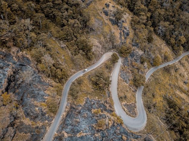 Toma aérea de una carretera con curvas en las montañas con árboles