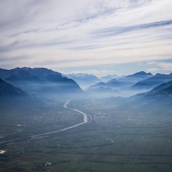 Toma aérea de una carretera con curvas hacia las montañas en la niebla bajo un cielo nublado