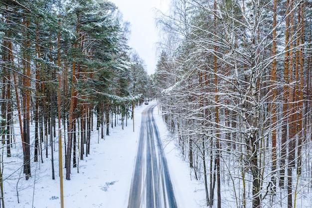 Toma aérea de la carretera de invierno a través del bosque