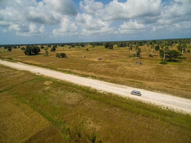 Toma aérea de una carretera rodeada de campos cubiertos de hierba capturados en zanzíbar, áfrica