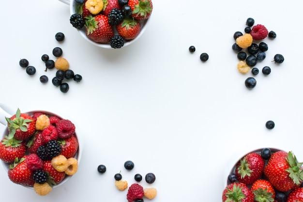 Toma aérea de coloridas bayas frescas saludables en tazas sobre un fondo blanco