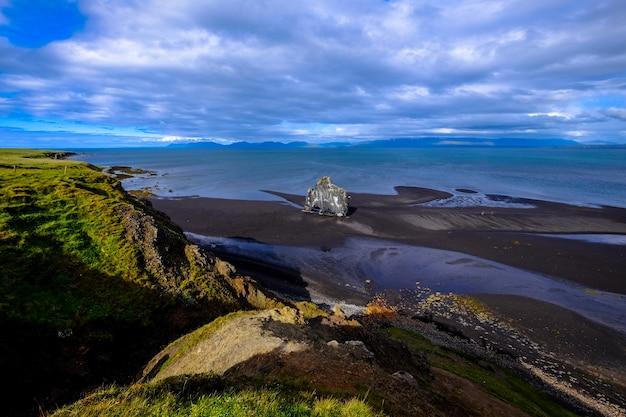 Toma aérea de la costa cerca de una colina cubierta de hierba bajo un cielo nublado