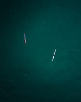 Toma aérea de dos kayaks navegando en mar abierto