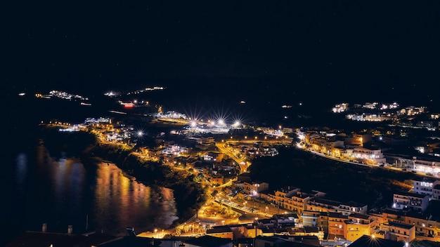 Toma aérea de edificios cerca del mar con luces encendidas durante la noche