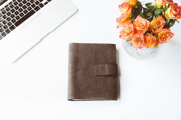 Toma aérea de un escritorio blanco con un cuaderno cubierto de cuero, un portátil y un jarrón de flores