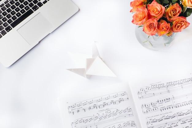 Toma aérea de un escritorio blanco con una hoja de música de origami de papel flores y una computadora portátil