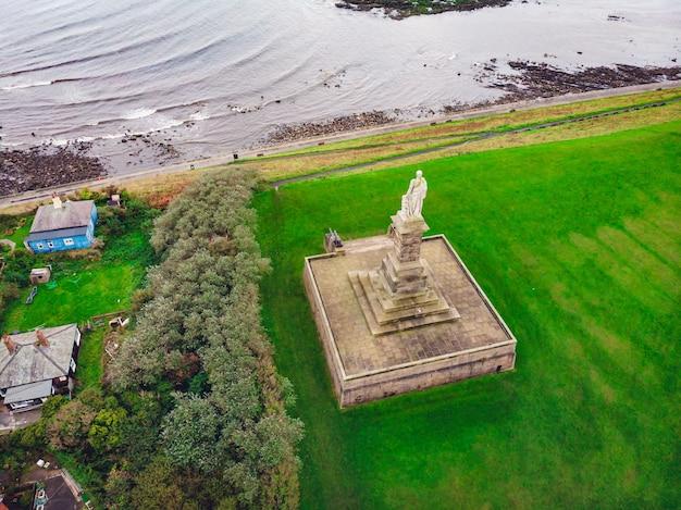 Toma aérea de una estatua en el valle verde cerca del mar
