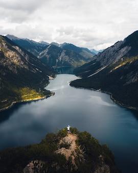 Toma aérea de un excursionista de pie en la punta de la colina mirando hacia el río entre montañas