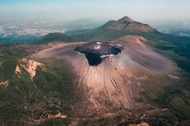 Toma aérea del fascinante cráter entre la vegetación