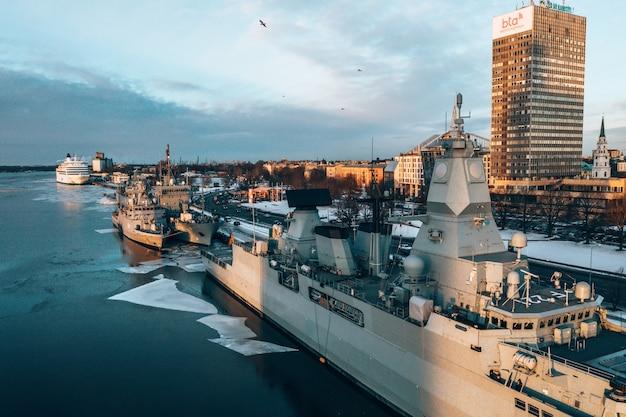 Toma aérea de grandes barcos militares en un puerto durante el invierno
