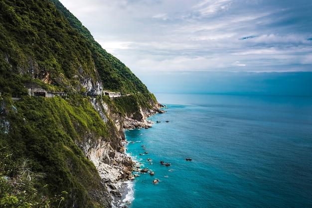 Toma aérea hermosa de acantilados boscosos cerca de un océano azul claro
